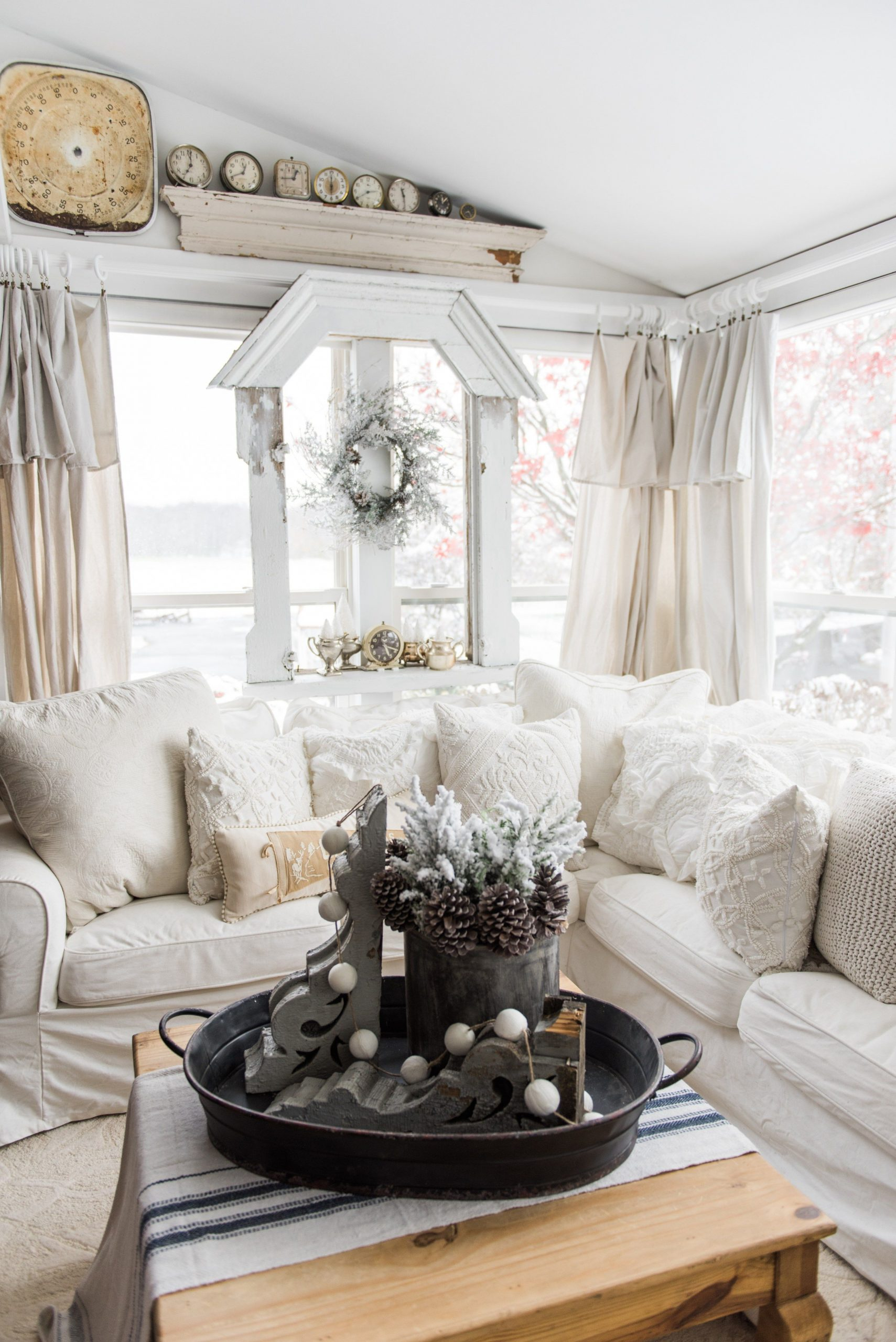 sunroom with cream drop cloth curtains wood table plush white sofa lots of light