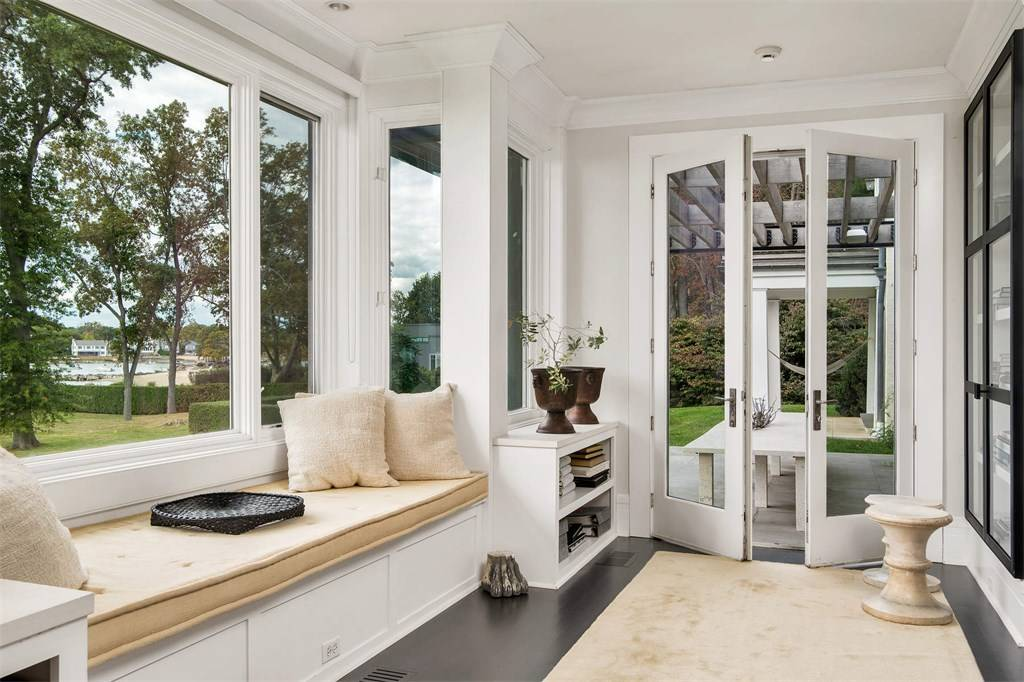 white custom sunroom with very dark wood floors built in window seat tan cushions and rug custom sunroom builder NJ Gambrick