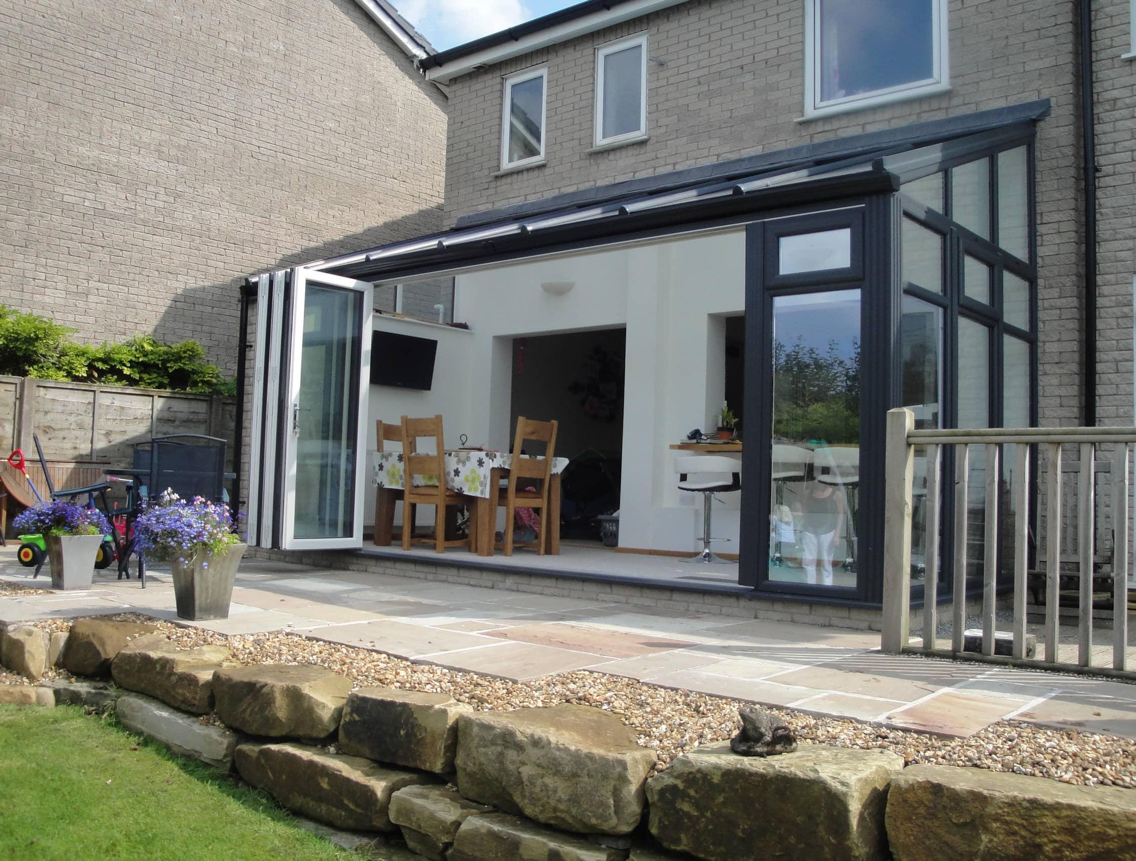 exterior view black and white folding doors custom sunroom nj custom sunroom builder Gambrick tile patio real stone