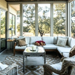 sunroom with glass walls and concrete floors wrap around cough area rug sliding doors custom sunroom builder nj