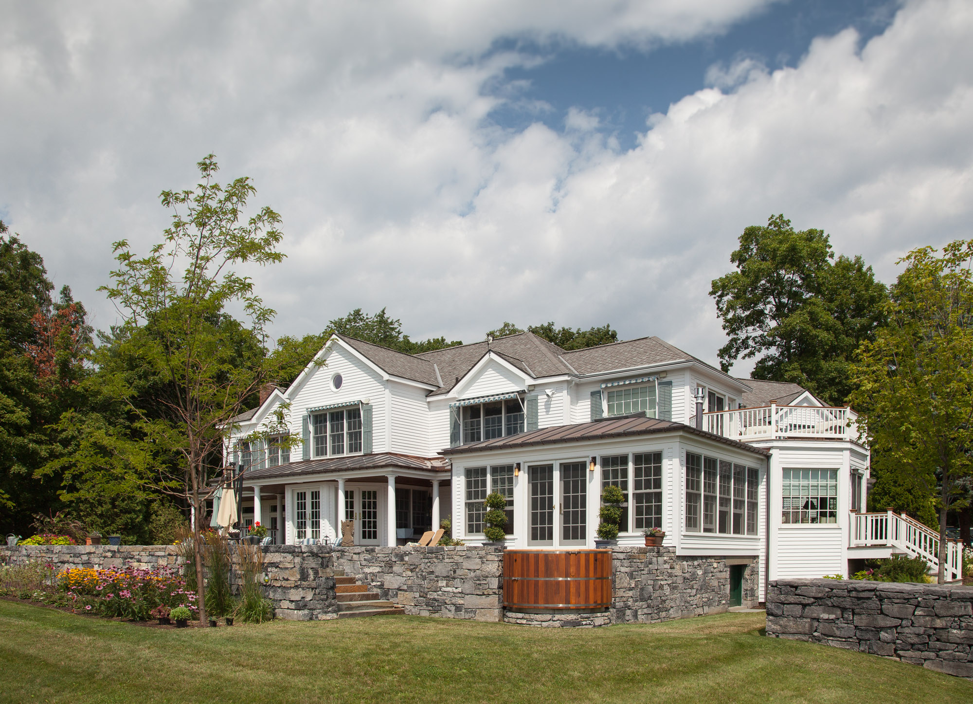 exterior sunroom view white siding and trim lots of glass real stone walls sunroom builder nj Gambrick