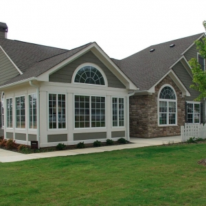 exterior view of sunroom gray siding with white trim arched windows stone veneer nj sunroom builder Gambrick