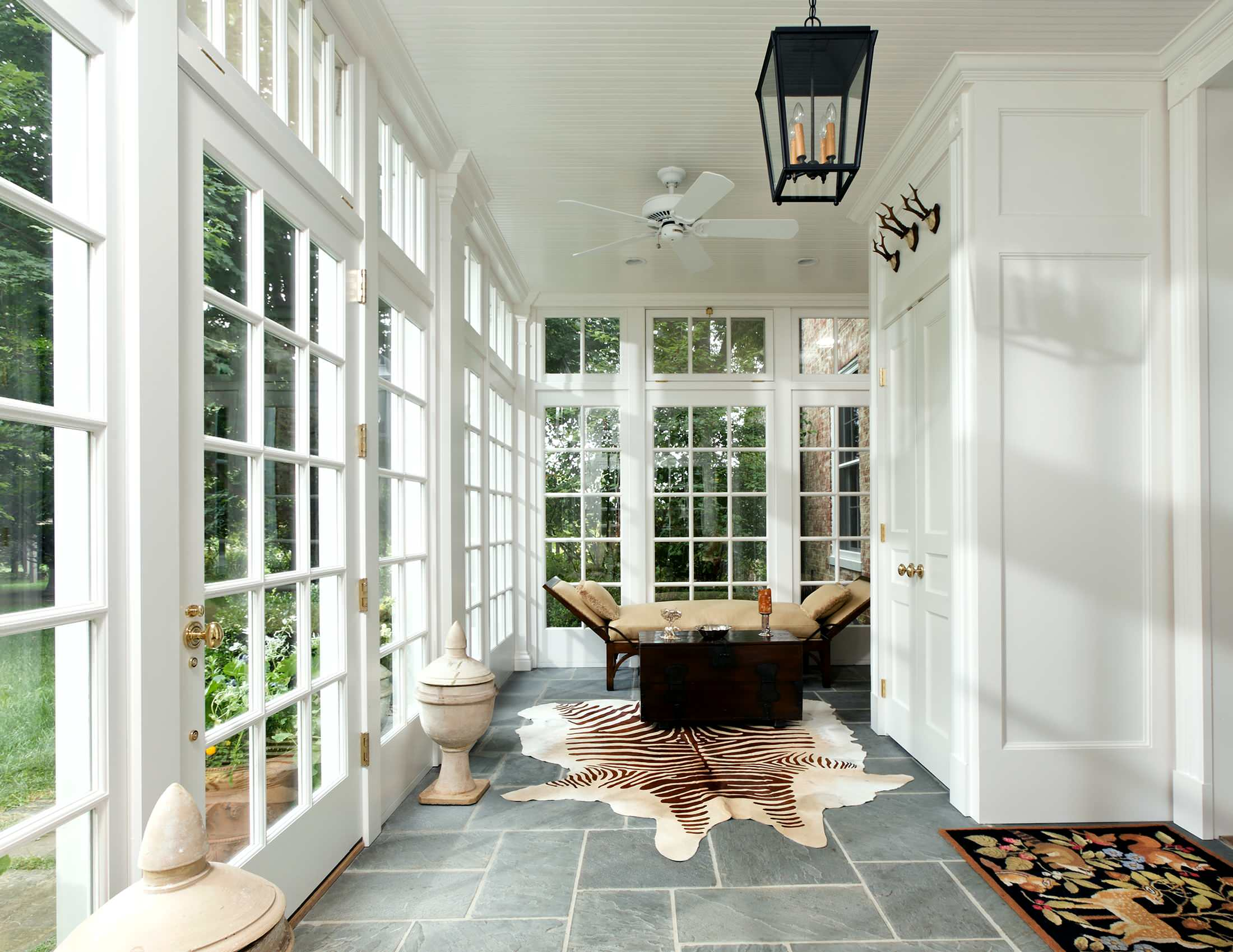 beautiful bright white sunroom with glass walls porcelain grey tile floors bead board NJ custom sunroom builder