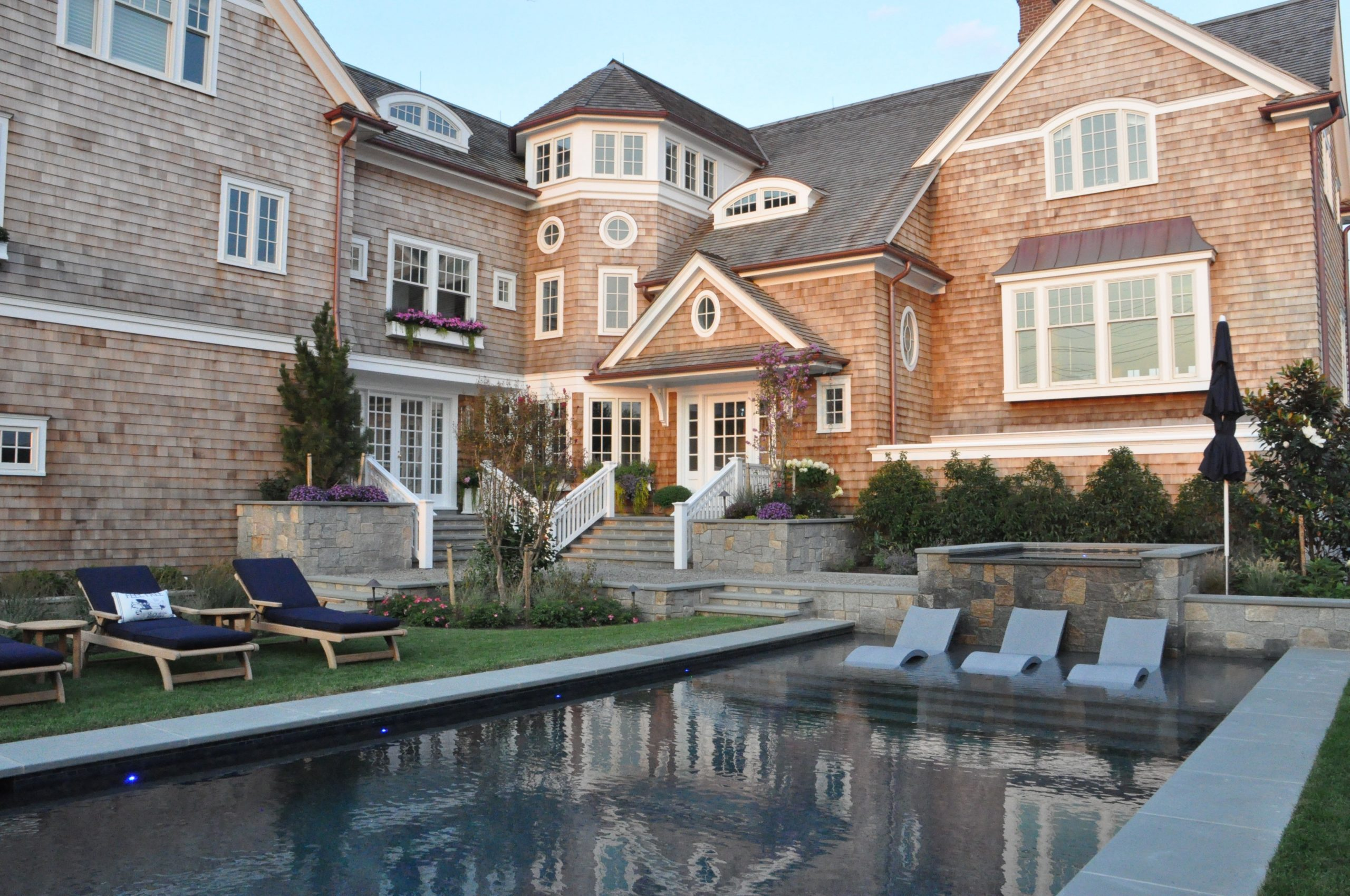Wood cedar shake siding with white trim and a brown shingled roof. Brown gutters. White front door. Brown stone veneer. Metal accent roof. In ground pool with blue stone border.