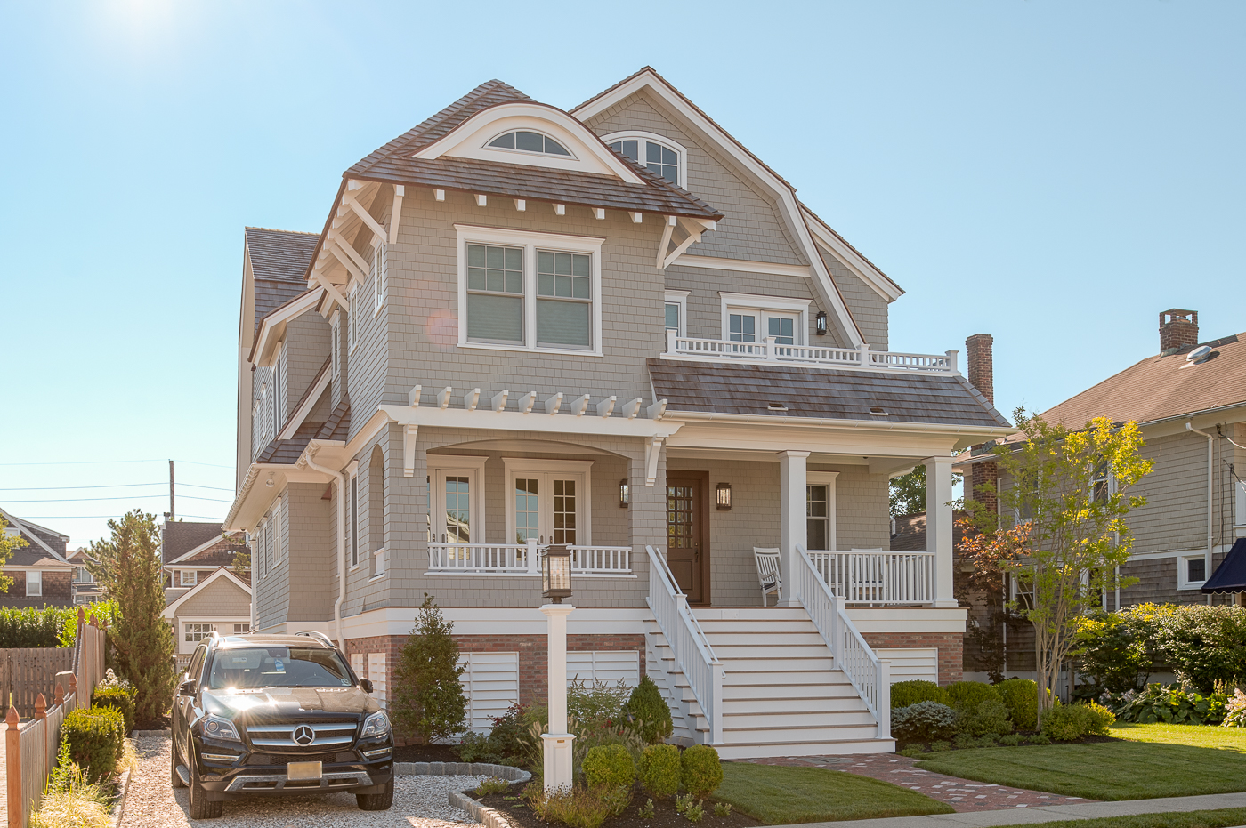 Light neutral colored tan siding with white trim, square columns and railings. Red brick veneer. Brown stained front door. Brown shingled roof. Beautiful beach house design.