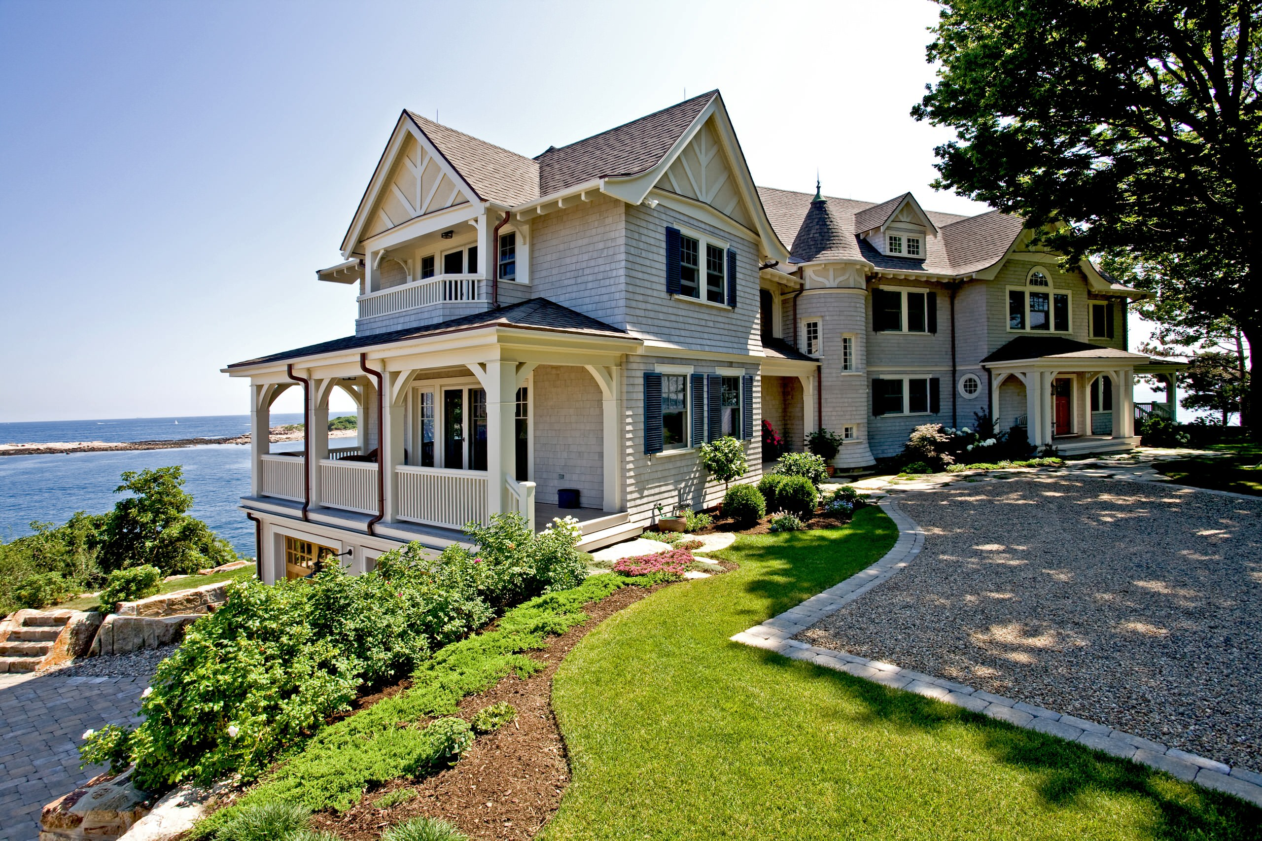 Natural cedar shake siding colors with square columns and white railings. White trim. Brown shingled roof. Brown stained wood doors. Gravel driveway. Beautiful waterfront custom home.