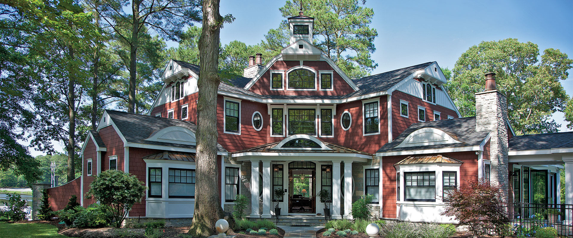 Red siding colors with white trim and wall paneling. White square columns. Light gray stone veneer and matching chimney. Black roofing shingles and metal accents. Black framed windows and doors.
