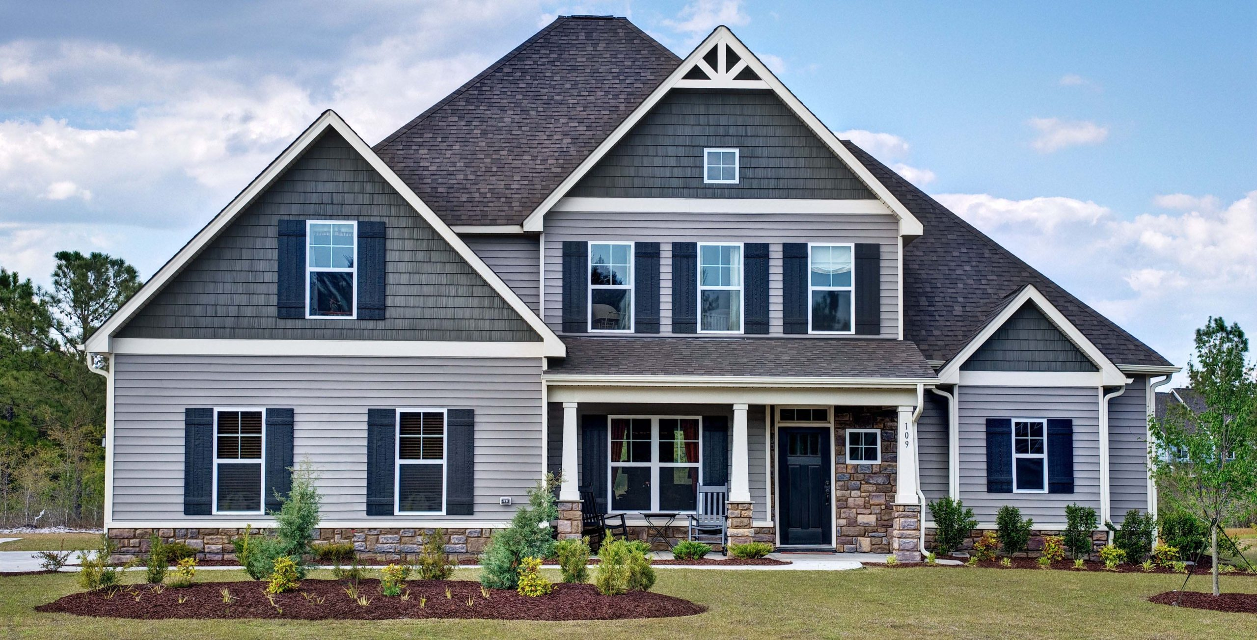 Two toned blue and gray siding colors with black front door. White trim with blue shutters. Brown stone veneer.