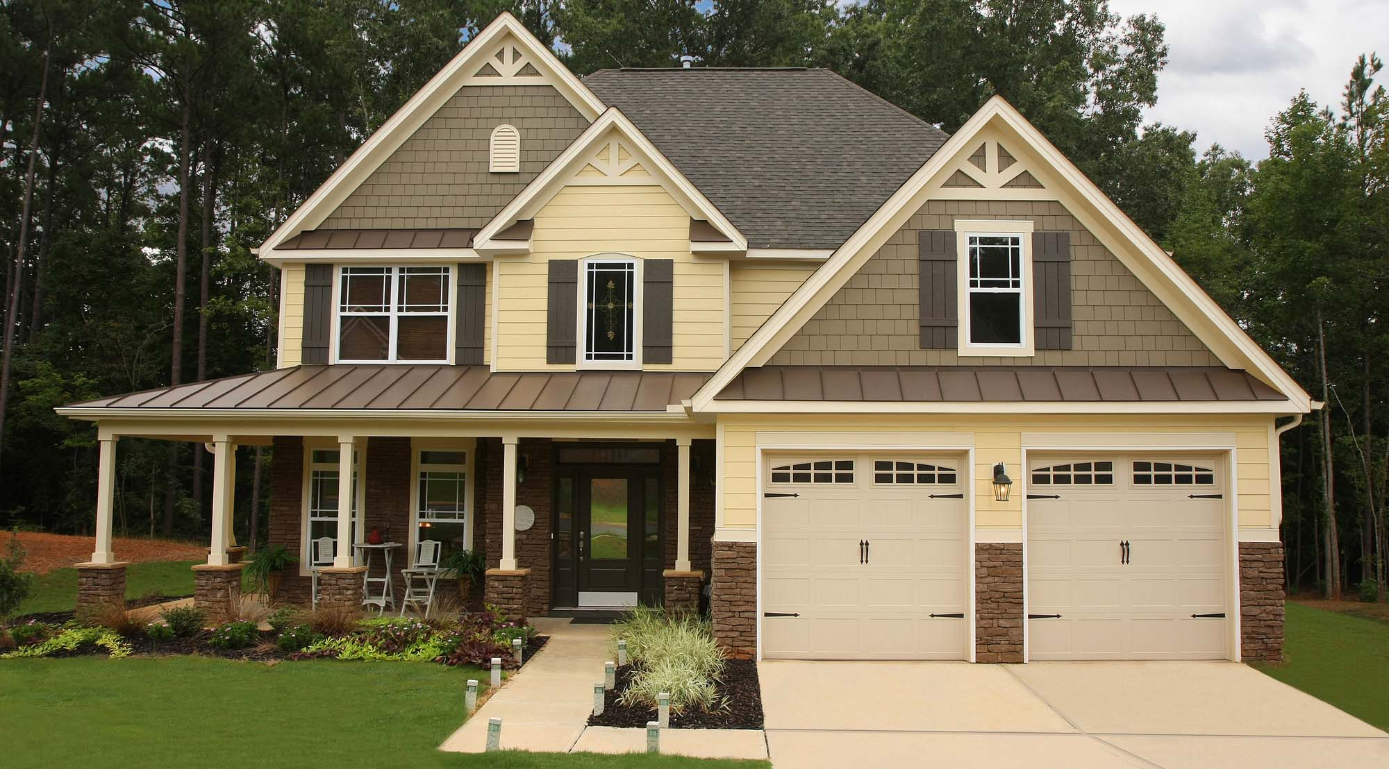 Two toned gray and pale yellow siding color combination. White trim and columns. Black roofing shingles with a brown metal accent roofline. White garage doors. Dark brown stained front door. Brown stone veneer. Gray shutters.