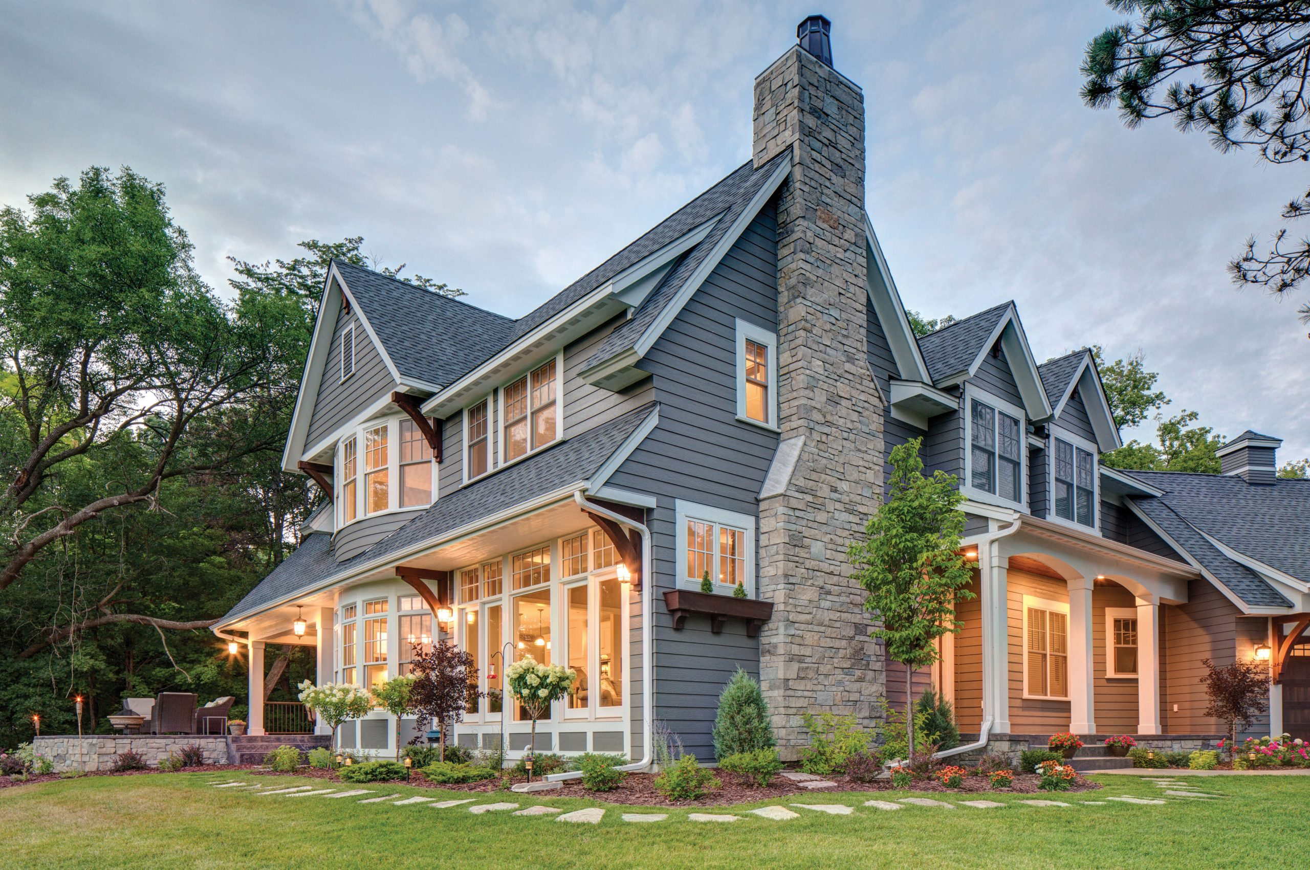 Blue gray siding colors with brown wood accents. White trim with white columns. Light brown stone veneer. Black roofing shingles.