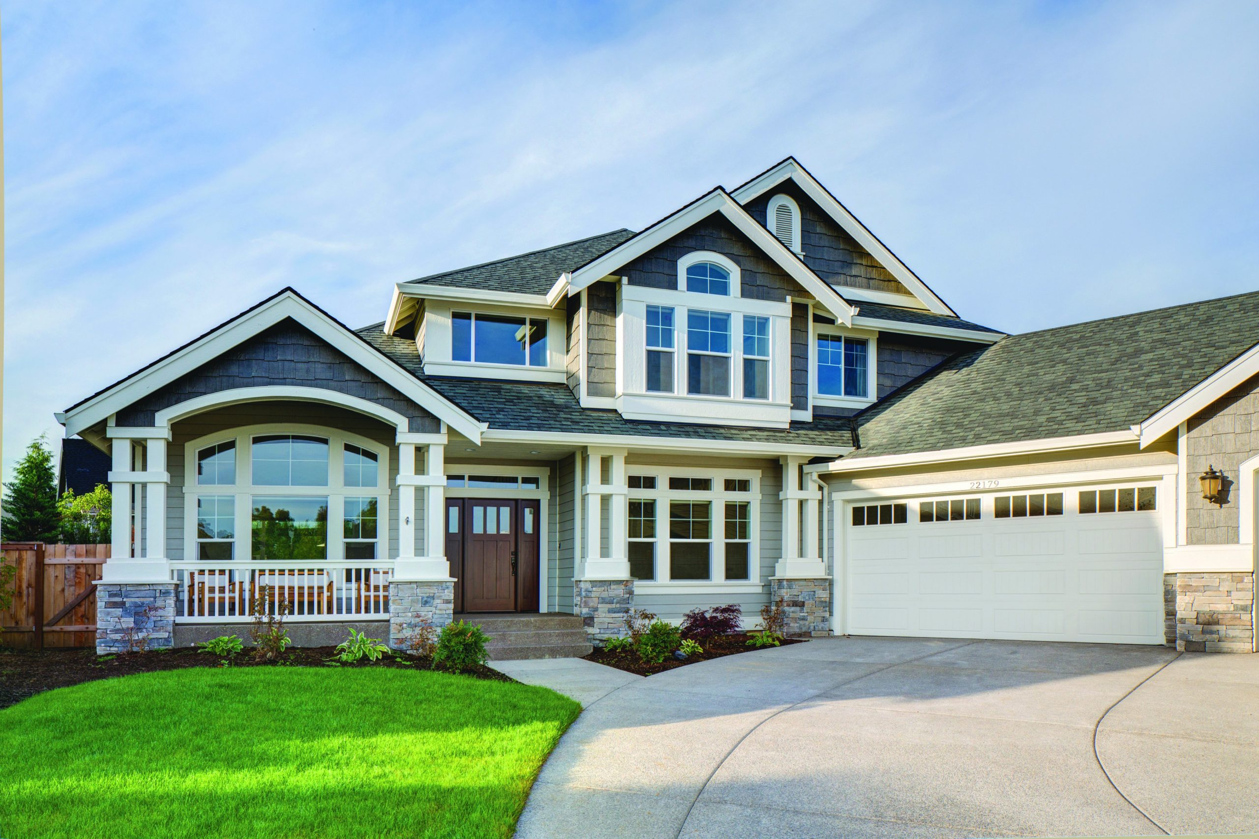 Two toned light and dark gray siding colors with white trim and columns with white railings. White garage doors. Dark brown stained front door. Light brown stone veneer.