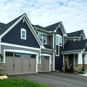 Two toned blueand gray siding color combination. Black roofing shingle. Taupe garage doors. Brown stone veneer. White trim and columns.