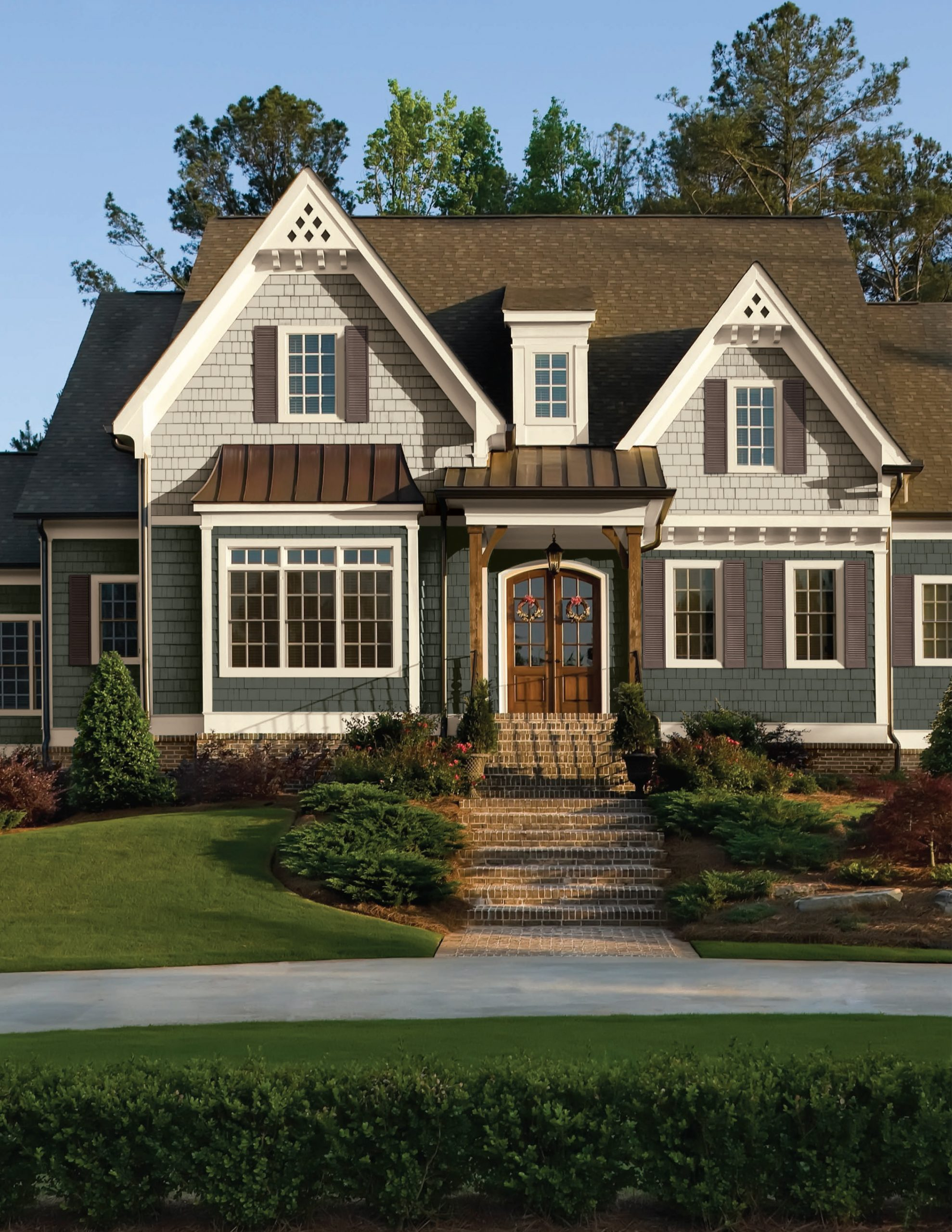Two toned white and blue gray siding colors scheme with black roofing shingles and black metal accents. Real wood columns. White trim. Stained brown real wood front door. Red brick veneer and steps.