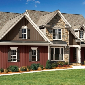 Red and brown two toned vertical siding colors with brown roofing shingles and black metal accents. White trim and columns with black metal railings. Brown stone veneer.