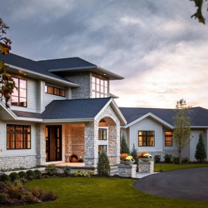 White vinyl siding with white stone veneer, black framed windows, darkly stained wood front door, beautiful custom home.