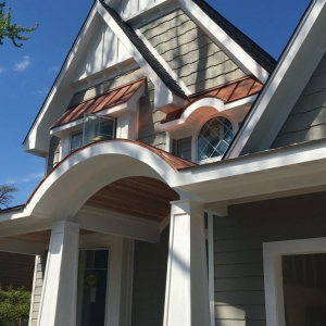 Gray siding colors with white trim. Brown metal roofing. Arched porch with tapered columns. Brown stone veneer.