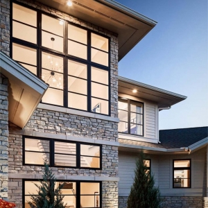 White horizontal vinyl siding with white stone veneer and black framed windows. Soffit lighting.