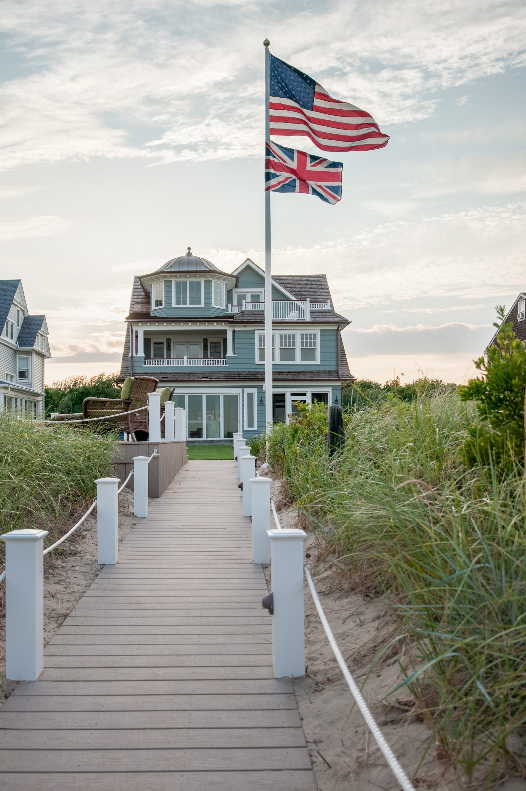 Blue house siding colors with brown shingle roof and white trim. White railings and columns. Metal accent roof. Beautiful ocean front custom home.