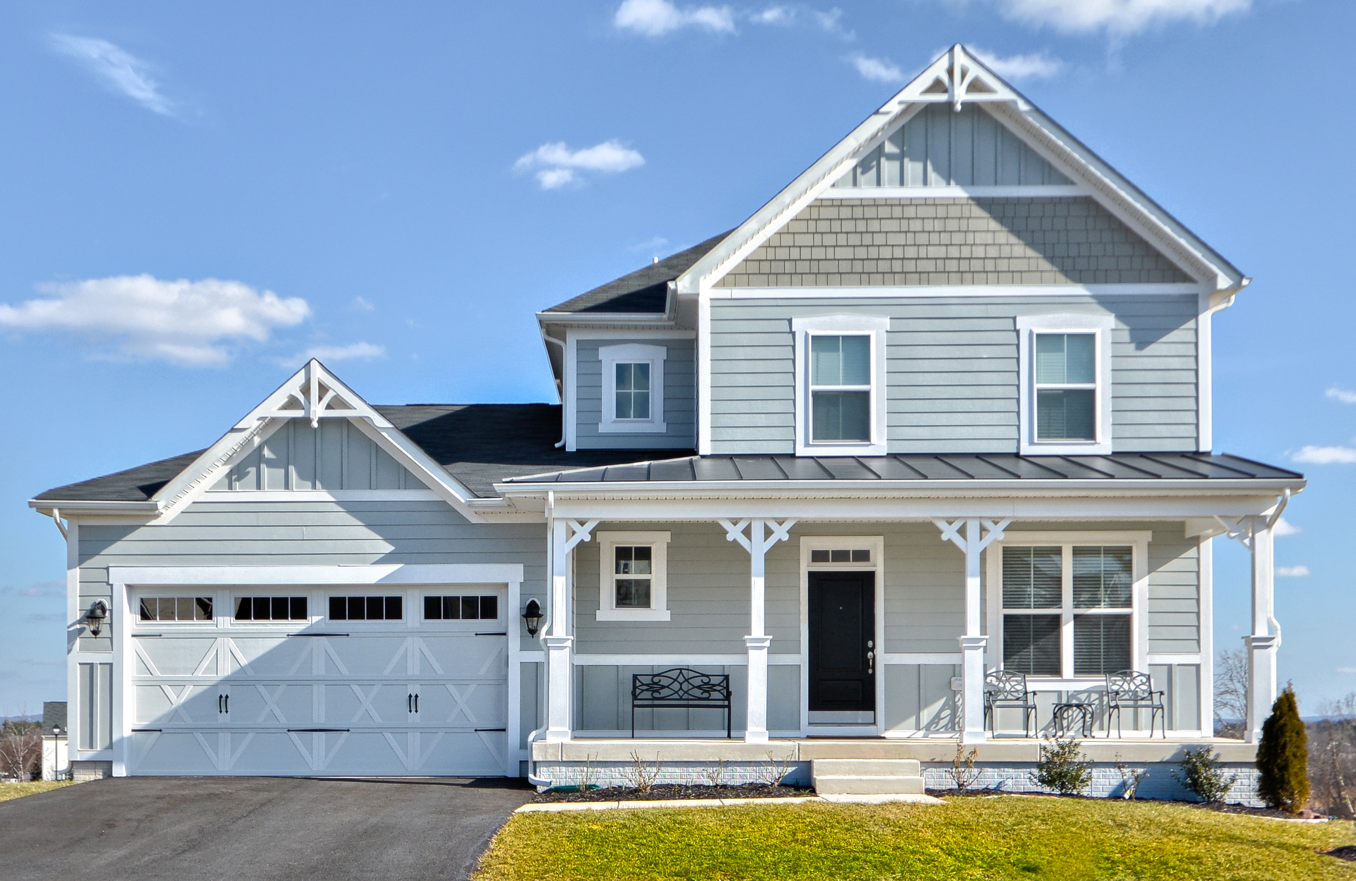 Blue, gray and white siding color scheme. White trim and columns. Black metal accent roof. Black shingled roof. Vertical siding accents. White garage door with black front door.