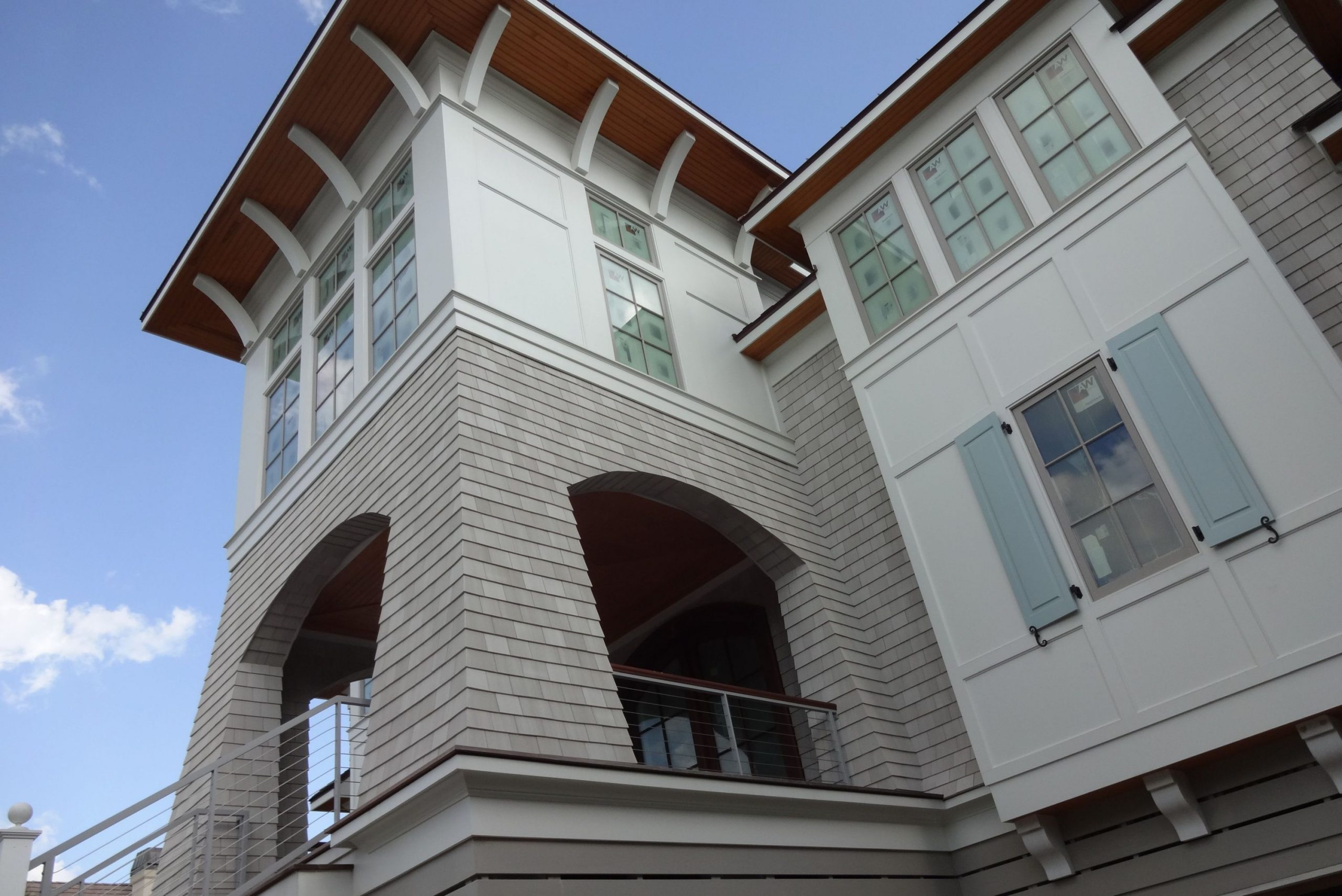 Light gray house siding colors with white trim and wall paneling. Real wood soffit. Modern wire railings with wood hand rail. Gray framed windows.