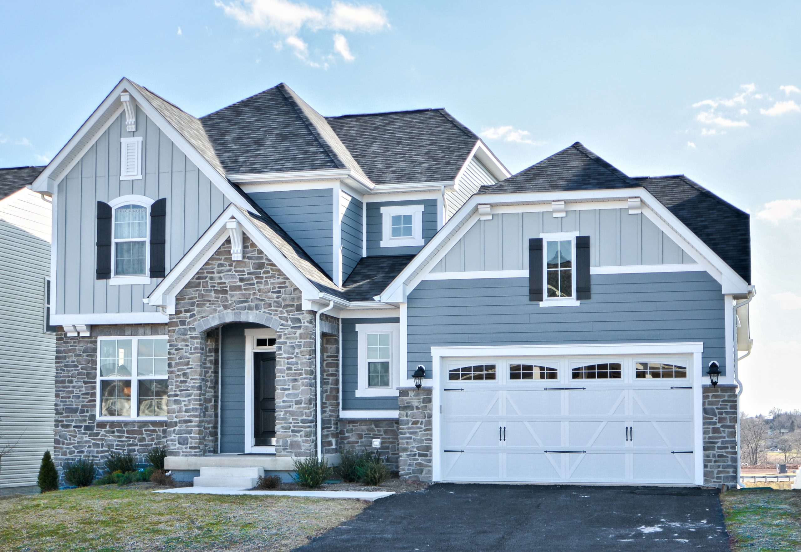 Two toned blue house siding color scheme. Medium blue with light blue siding. Brown stone veneer. Black front door with white garage doors.