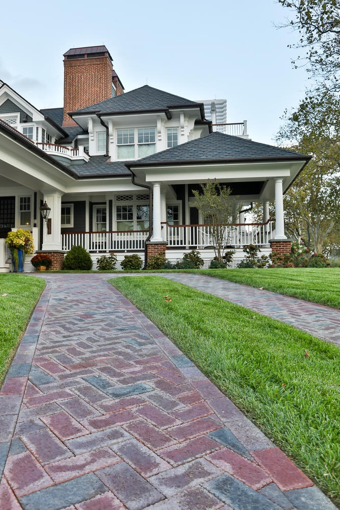 Dark gray siding colors with thick white trim and columns. White railings with a wood hand rail. Brick paver walkway. Dark shingle roofing with brown gutters. Brick column bases.