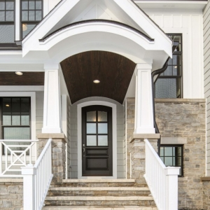 Light gray siding color with tons of white trim and white wall paneling. Dark brown wood porch soffit with recessed lighting. Tapered porch columns with white rails. Stone veneer. Black gutters. Black framed windows.
