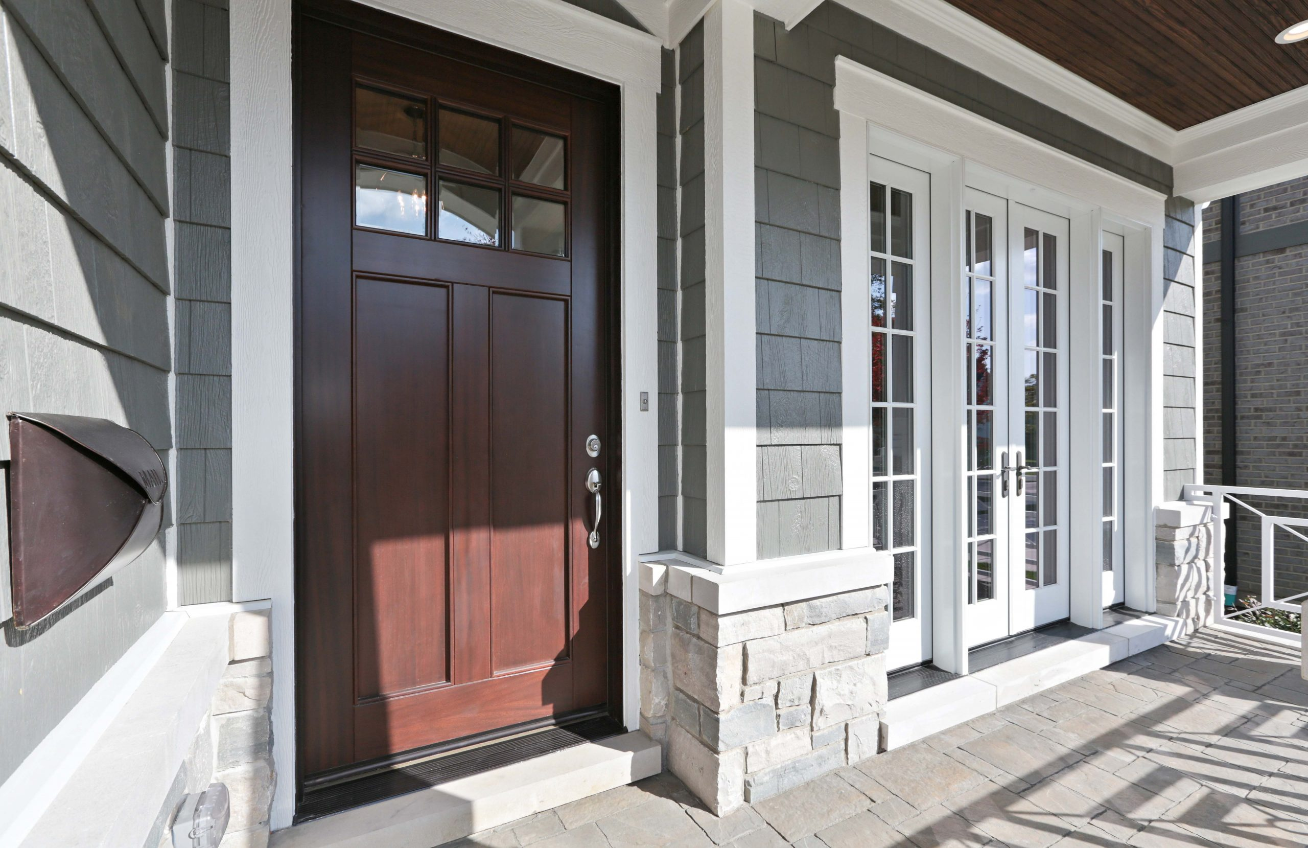 Gray vinyl siding with white trim. Dark brown porch soffit with recessed lighting. Dark brown stained front door. Light gray stone veneer. Paver porch top.