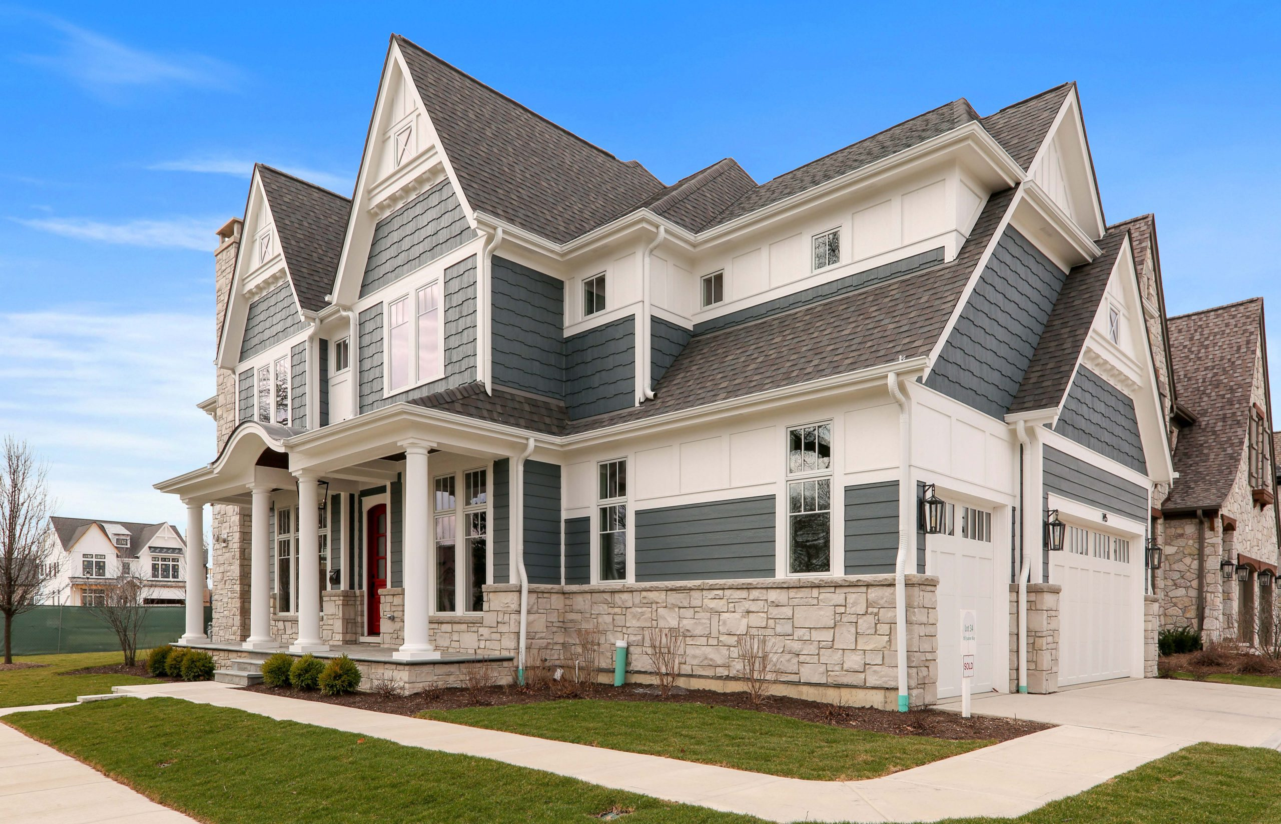 Blue vinyl siding with white wall paneling and trim. Round porch columns. Light tan stone veneer. Red fron door. Gray shingle roofing. White garage doors.