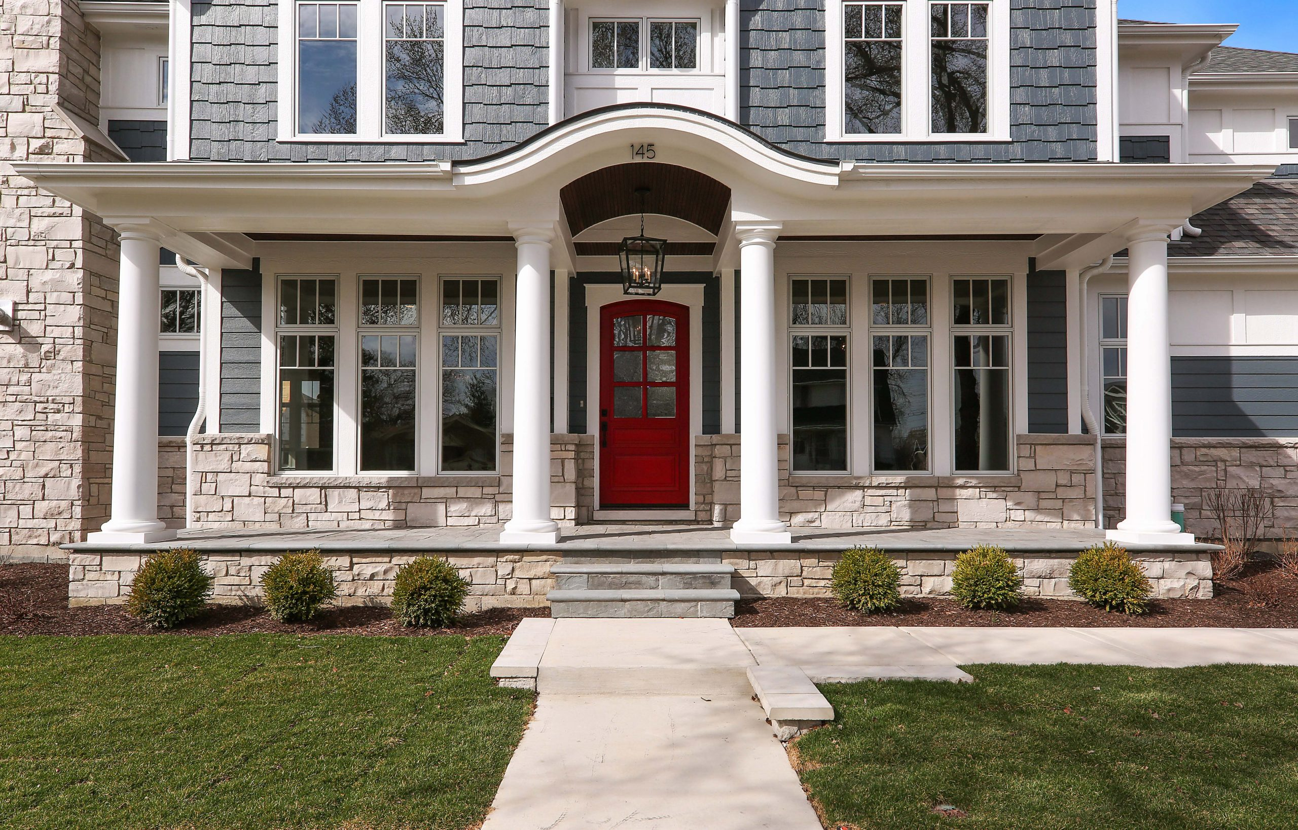 blue vinyl siding color with white trim, wall paneling and round columns. Red front door. Dark brown wood porch soffit. Light brown stone veneer. Concrete walkways.