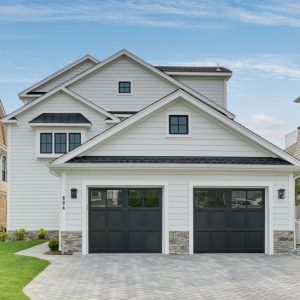 White lap siding colors with black shingle roof, black metal accent roof, black framed windows, black garage doors, light gray stone veneer. Transitional home design. Light gray paver driveway.