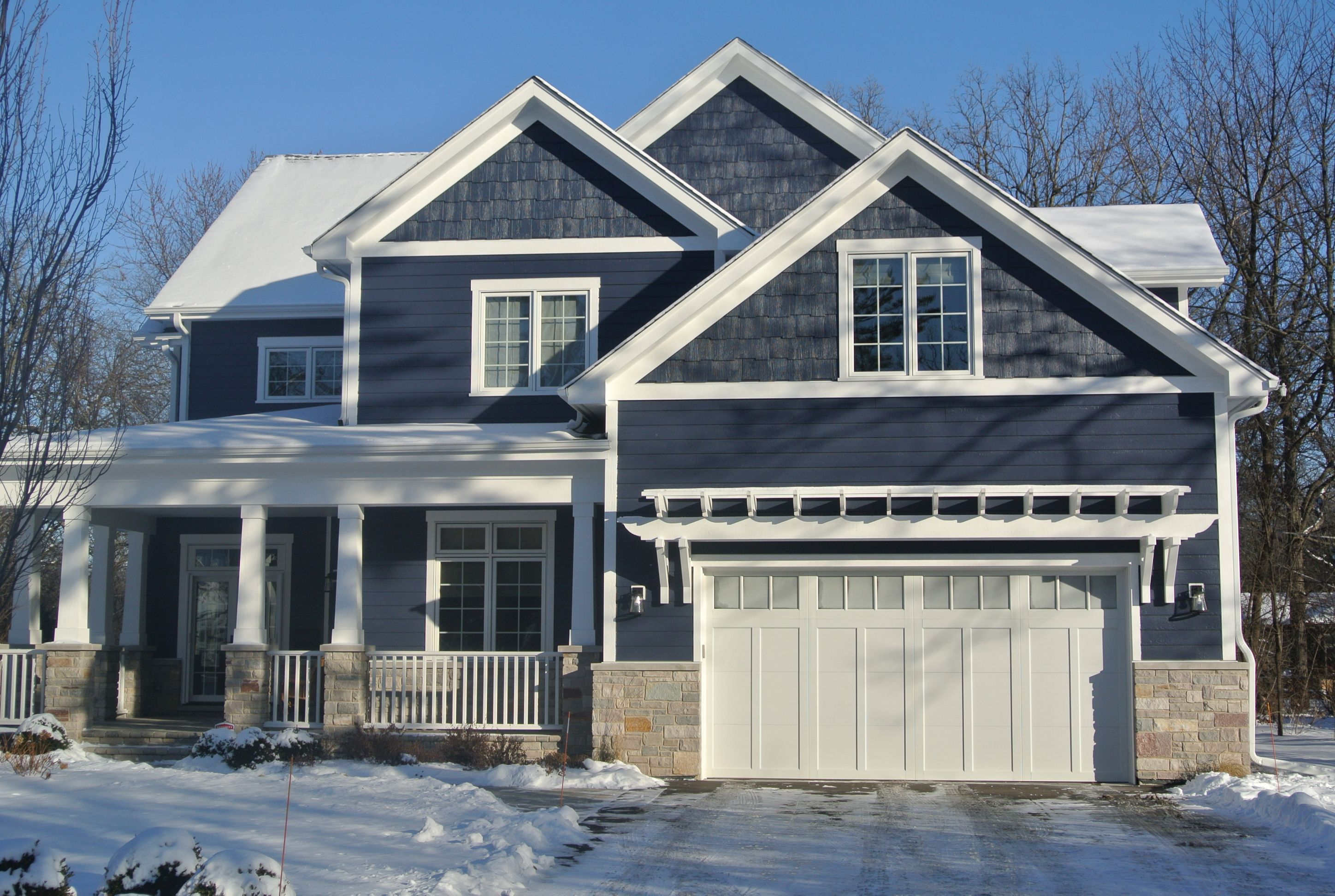 Dark blue colored siding with white trim. White tapered porch columns with white railings. Natural light brown stone veneer. White gutters. White garage doors.