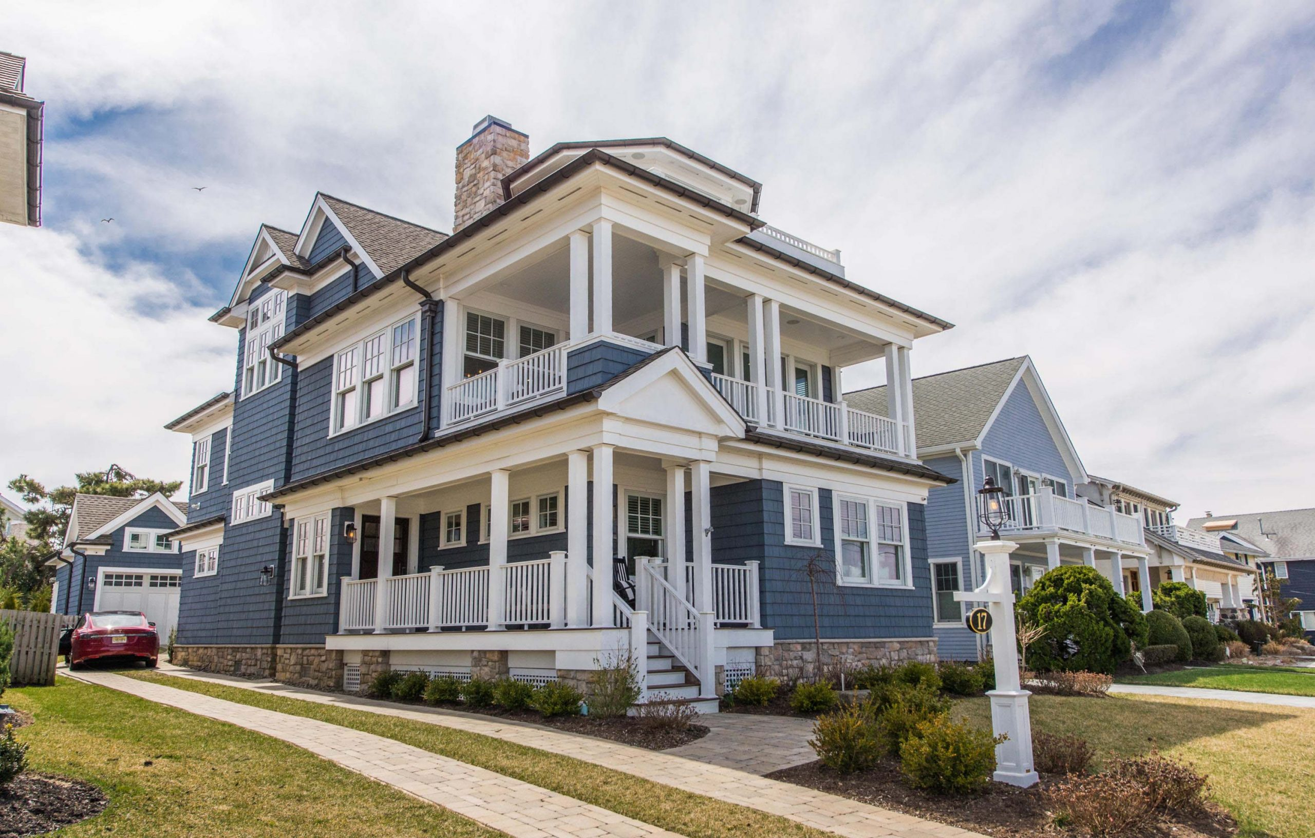 Blue vinyl siding colors with white trim. White wall panels. White square porch columns with white railings. Brown stone veneer. Black front door. Brown gutters. Brown stone veneer chimney with metal cap.