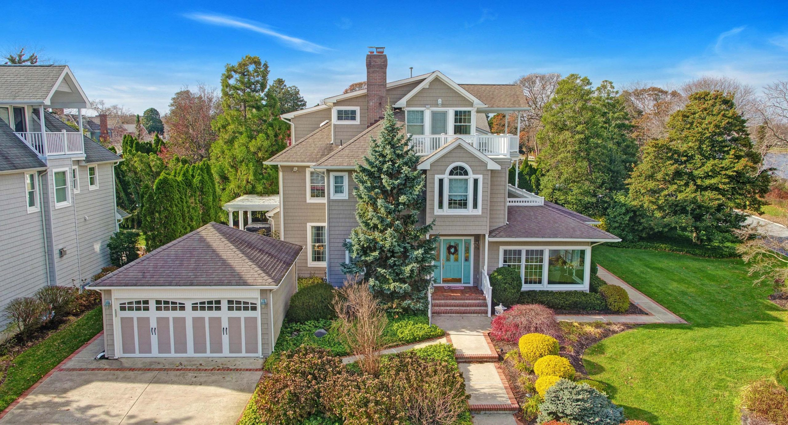 Tan vinyl siding colors with white trim. White railings. Red brick veneer and chimney. Teal blue front door. Concrete driveway and walk with red brick trim.