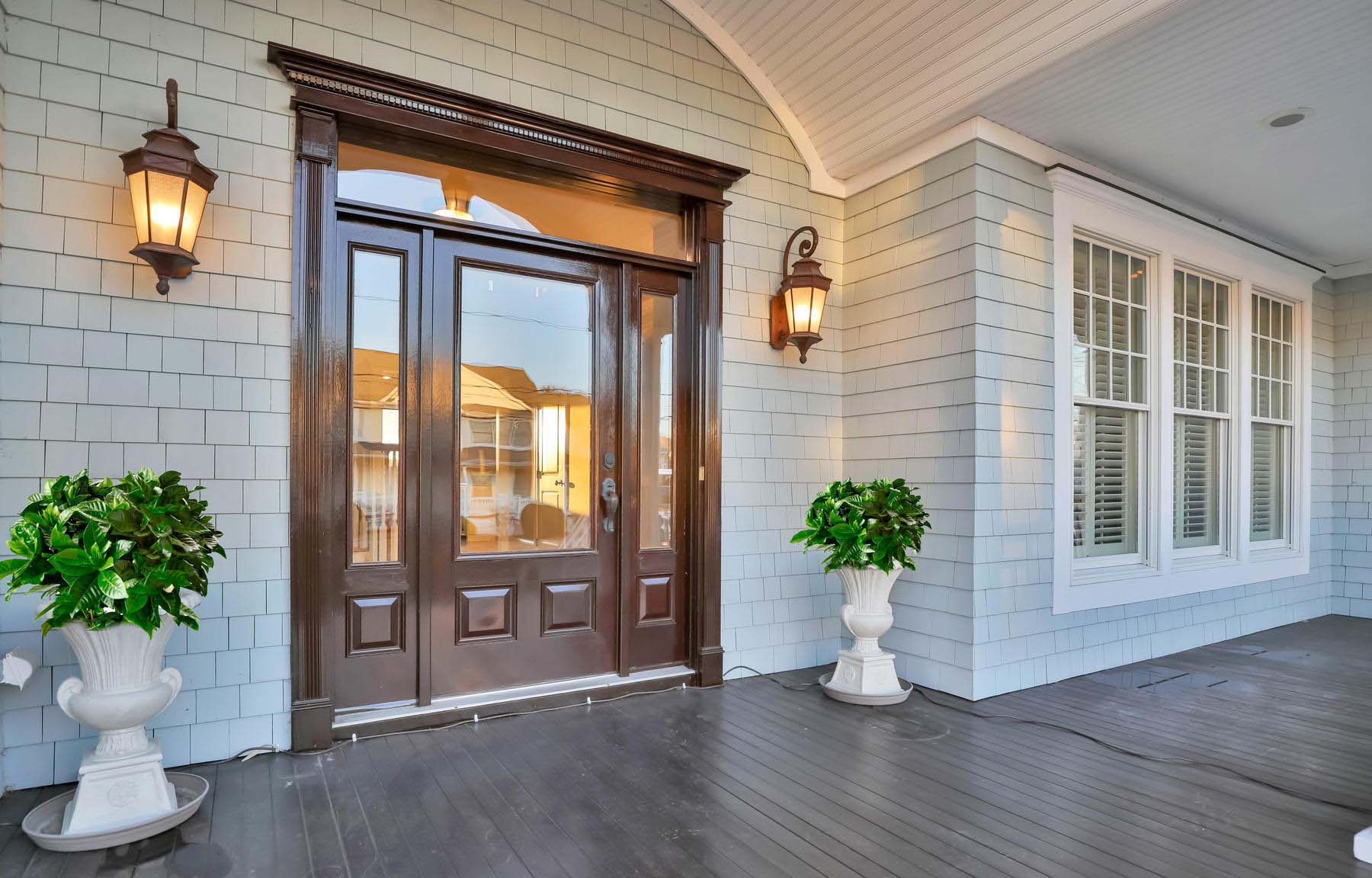 Front porch with light gray cedar shake siding, dark brown stained wood front door, white trim and soffit with recessed lighting. Dark brown stained wood front porch.