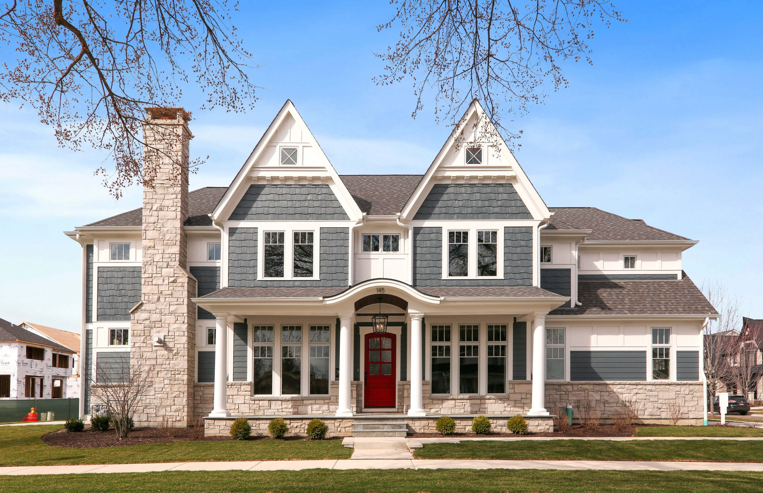 Blue Colored house. Cedar shake siding. Red front door with white trim and columns. Light colored stone veneer. Azek wall paneling.