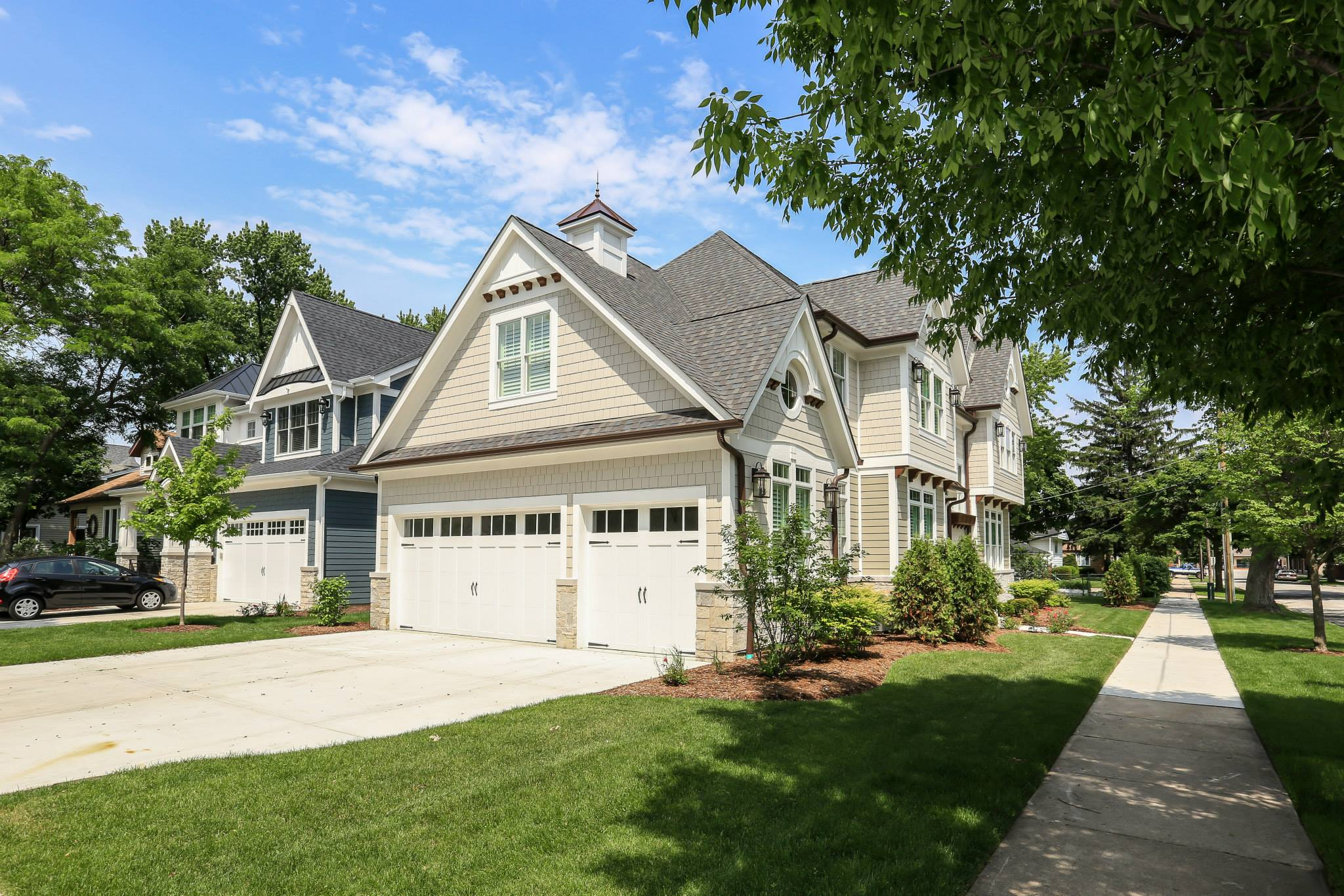 Cream colored cedar shake siding colors with brown gutters and black shingled roof. White trim and wall paneling. White garage doors. Light stone veneer. Concrete driveway and walk.