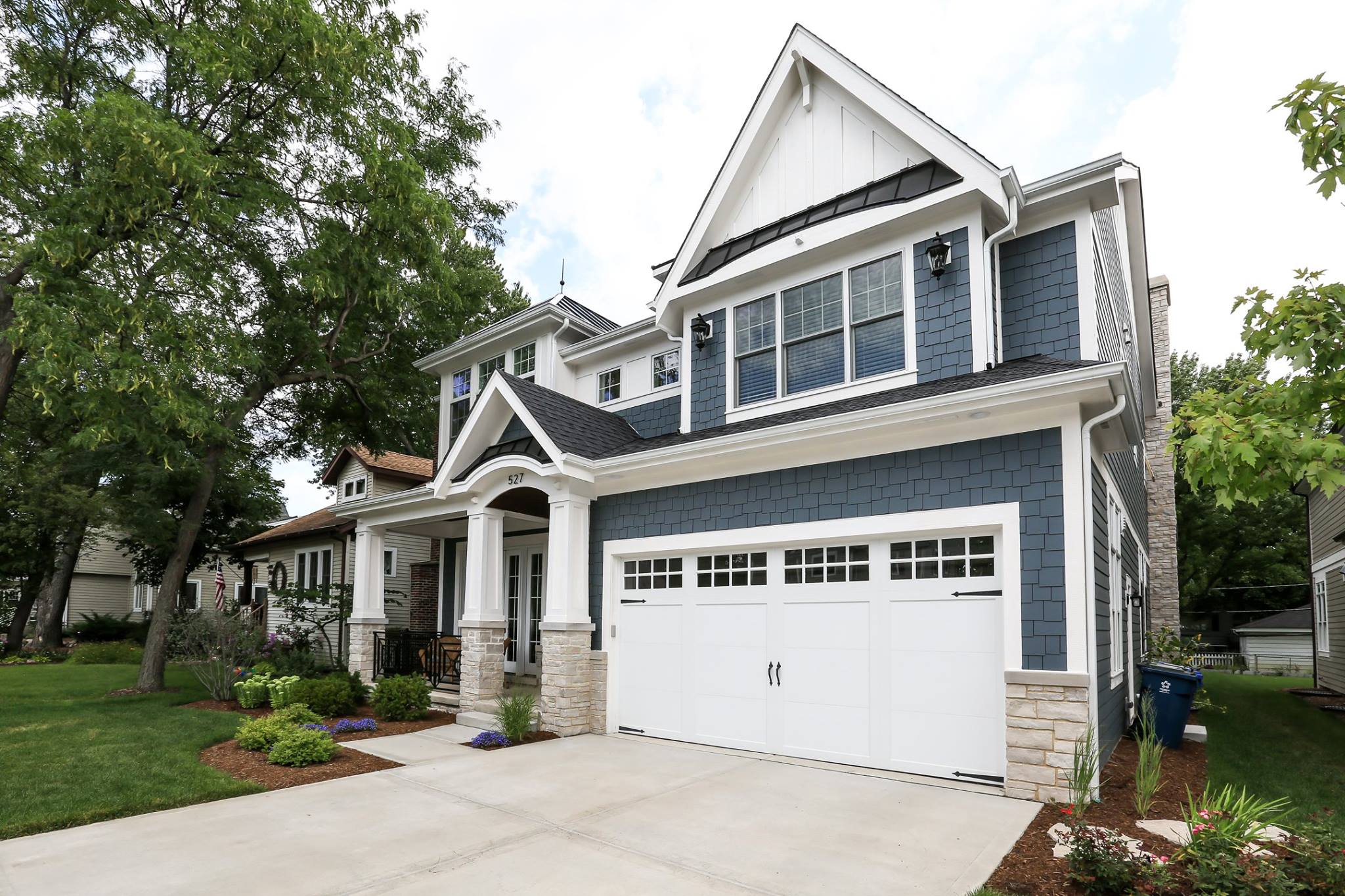 Blue vinyl siding colors. Light tan stone veneer. White garage door. White trim and wall paneling with blakc metal accent roof. Black shingled roof. Tapered porch columns. Black porch railings.