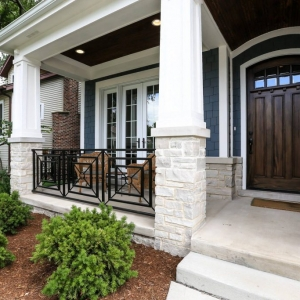Blue siding color with brown stained front door. Black porch railings with white tapered porch columns. Concrete porch and steps. Light stone veneer. Dark brown stained wood porch soffit with recessed lighting.