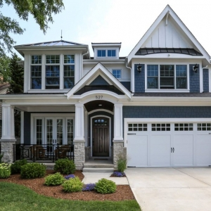 Blue cedar shake siding colors with white trim and wall paneling. Black shingled roof with metal accents. Dark brown stained wood front door with white garage doors. Light stone veneer. Dark wood stained porch soffit with recessed lighting. Concrete driveway.