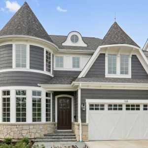 Blue gray siding colors with dark brown front door. Azek wall paneling. White garage door. Light tan stone veneer siding. Dark gray shingle roof.
