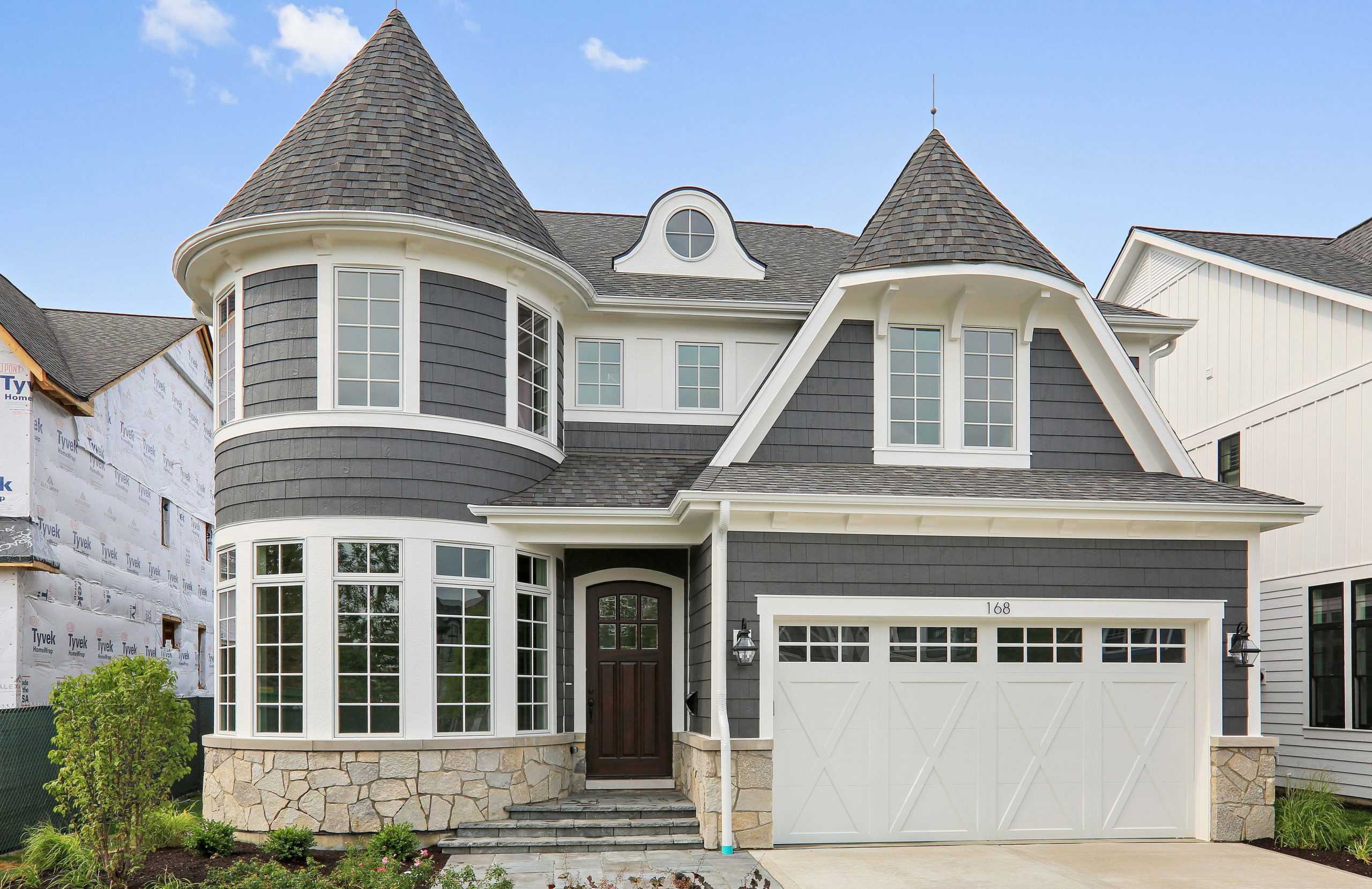 Blue gray siding colors with dark brown front door. Azek wall paneling. White garage door. Light tan stone veneer siding. Dark gray shingle roof.
