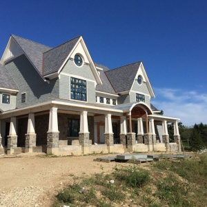Light gray cedar shake siding with white trim and wall paneling. Tapered porch columns with stone veneer bases. Black framed windows. Brown stone veneer.