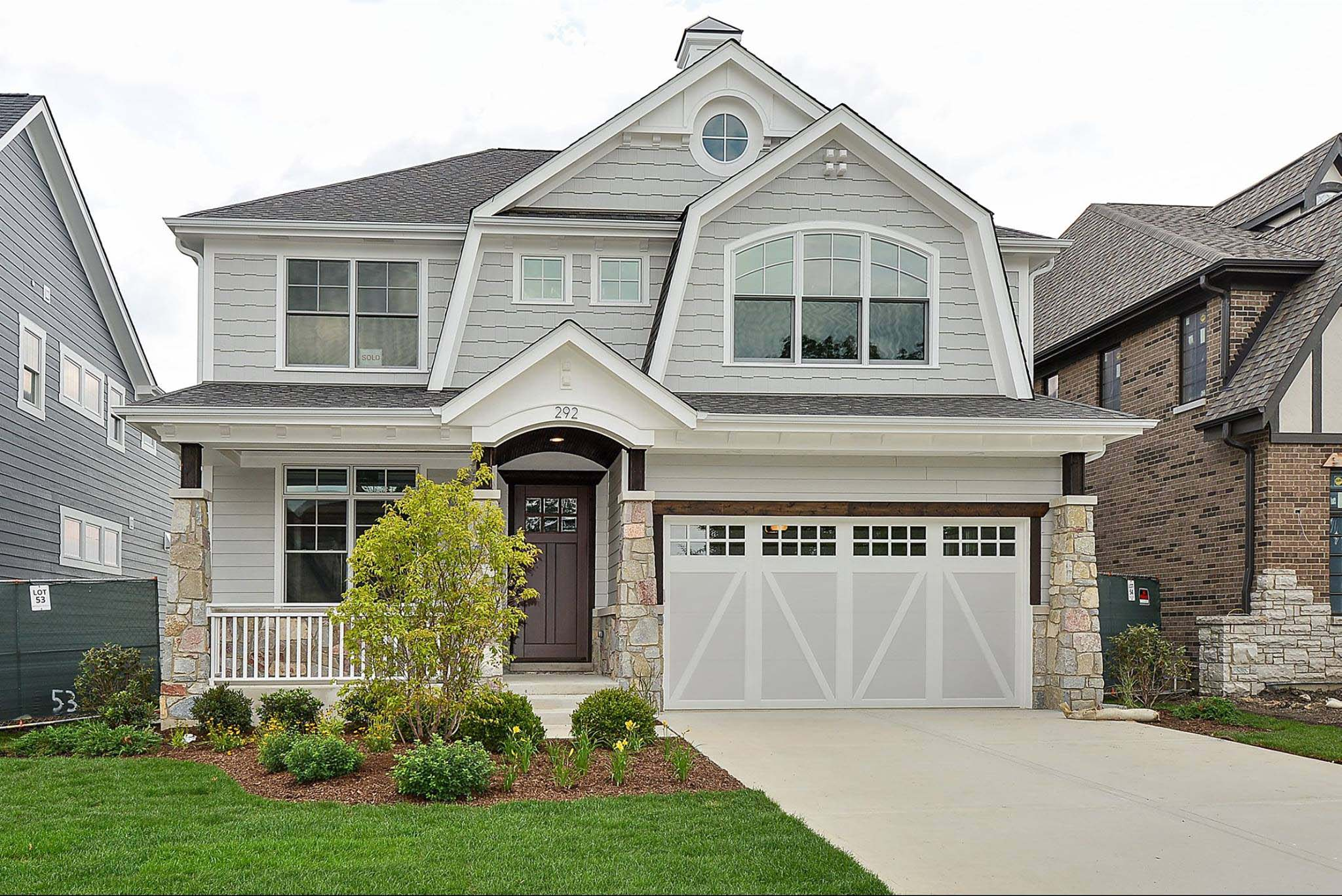 Light gray siding colors with white trim and wall paneling. Dark brown front door. Light brown stone veneer. Concrete driveway and porch. White railings. White and gray garage doors. Dark brown wood stained porch soffit. Black shingled roof.