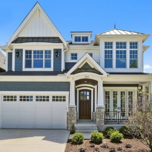 Blue vinyl siding colors with white trim and wall paneling, black metal roofing, brown stained wood front door, white tapered columns, light brown stone veneer, black railings, concrete driveway and walk.