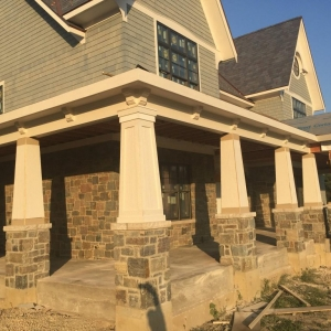 Light gray cedar shake siding colors, white tri with tapered porch columns, light brown stone veneer, blue shingled roof, concrete front porch top.