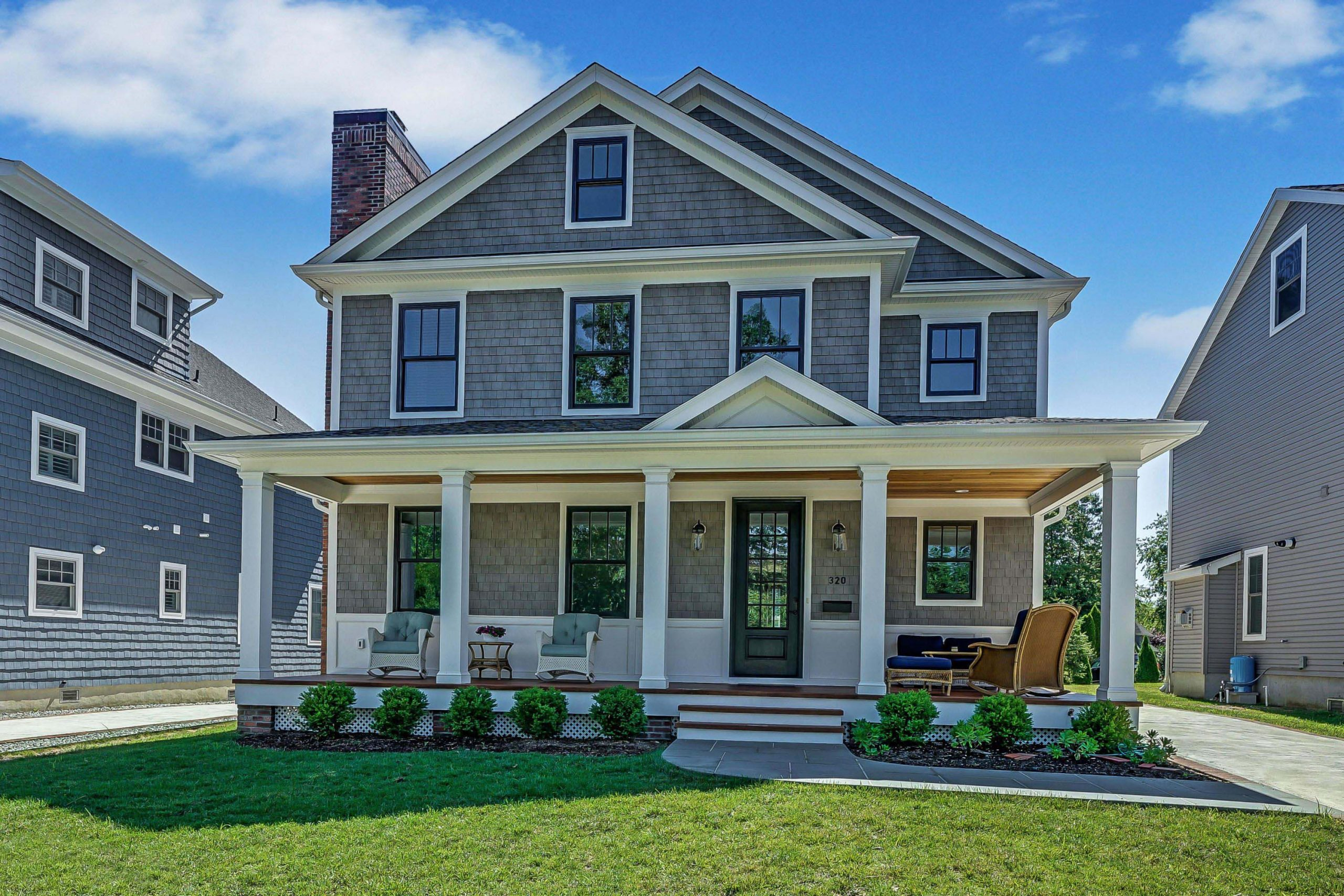 Natural gray cedar shake siding color with white trim and black framed windows, white wall paneling, wood decking, black front door, red brick chimney veneer, wood porch soffit, blue stone walk.