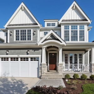 Light gray cedar shake vinyl siding with Azek trim, light colored stone veneer, brown real wood front door, black metal accent roof. White garage door.