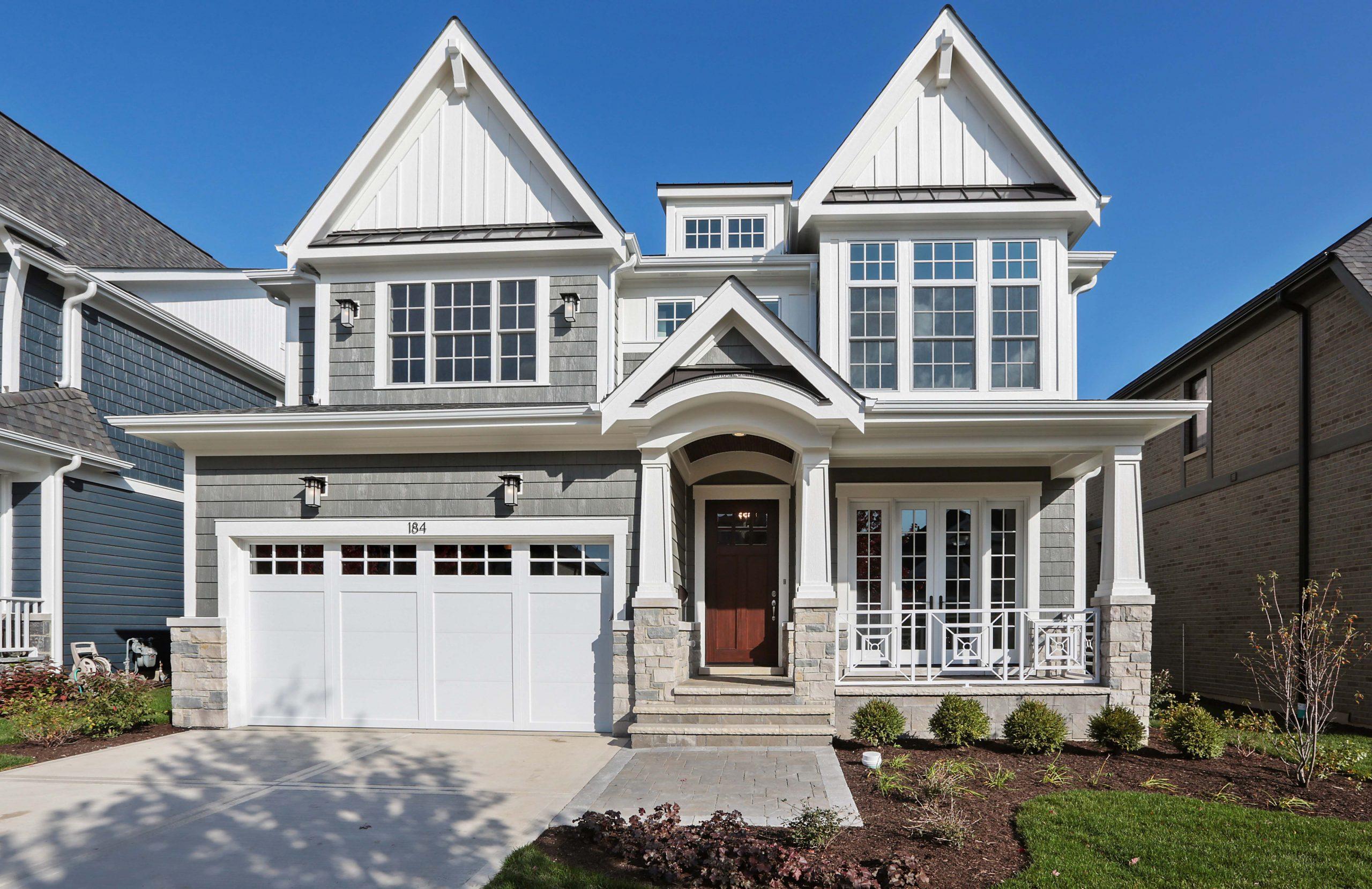 Light gray cedar shake vinyl siding with Azek trim, light colored stone veneer, brown real wood front door, black metal accent roof. White garage door.