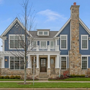 Blue siding colors with brown stone veneer. White trim with square coluns and arbor. Stone chimney. Black shingled roof.